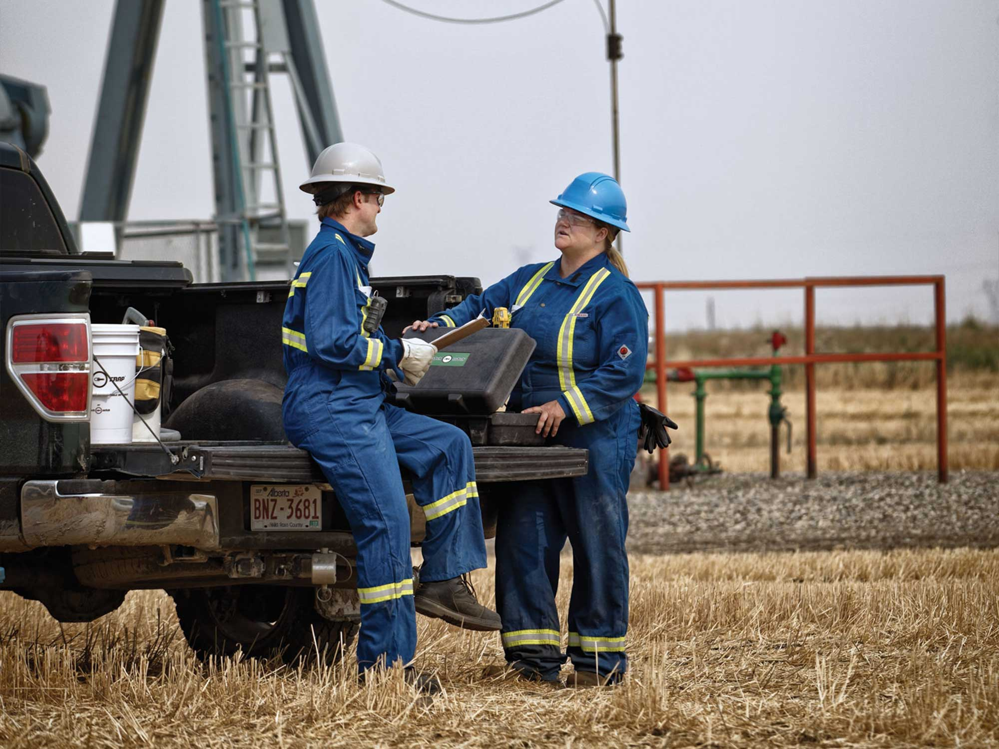 Brand photography for Energy Safety Canada by Jason Stand of two workers in front of an oil derrick on a truck talking by studio forum