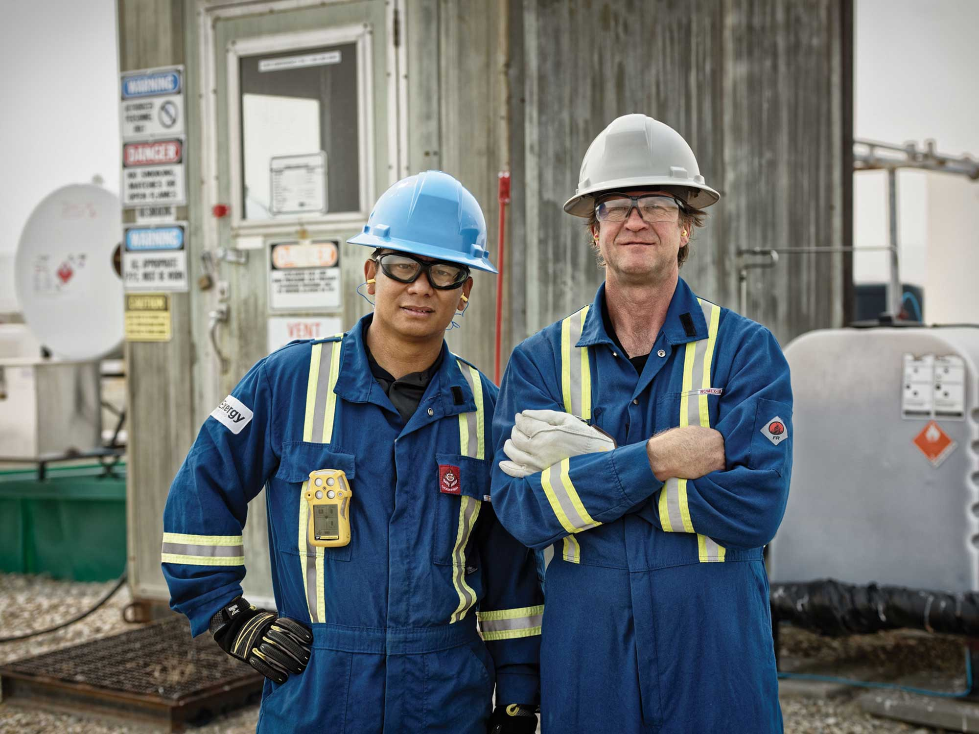 Brand photography for Energy Safety Canada by Jason Stand of two workers together on an oil and gas worksite by studio forum