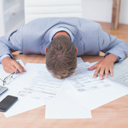 Man face down on a table covered in tax documents