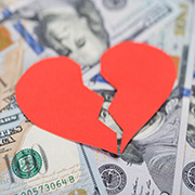 Paper cutout of a broken heart on top of $100 bills