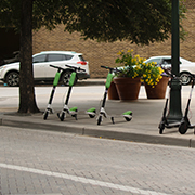 3 scooters on the sidewalk