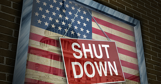 "American flag with a ""shut down"" sign displayed over it"