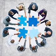 Group of people standing around a circular table putting together giant puzzle pieces