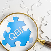 "Magnifying glass hovering over a missing jigsaw puzzle piece that says ""QBI"""