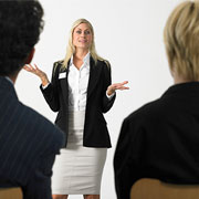 Businesswoman talking to 2 people sitting in front of her
