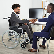 Businessman in a wheelchair shaking the hands with another businessman