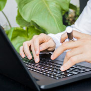 Person typing on a laptop while holding a vape pen