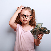 Young girl wearing glasses holding a fistful off dollars