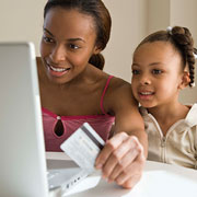 2 girls looking at a laptop and holding a credit card