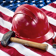 Construction hat and a hammer on the American flag