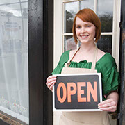 Business owner holding 'open' sign