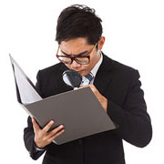 Businessman with magnifying glass reviewing a notebook