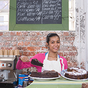Young girl holding a piece of cake behind a bakery counter