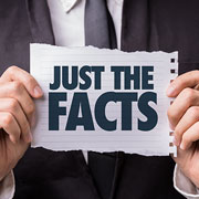 """Just the Facts"" sign being held up by a businessman"