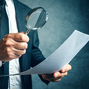Man examining paper with magnifying glass