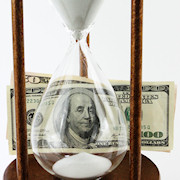 Hourglass with hundred dollar bills