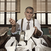 Businessman behind a desk covered in papers