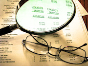 Glasses, magnifying glass, and financial spreadsheet