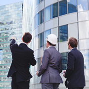 3 businessmen looking at a skyscraper