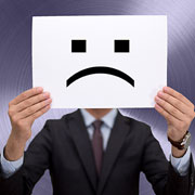Businessman holding up an unhappy face picture