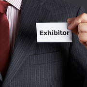 Businessman with name tag labeled 'Exhibitor'