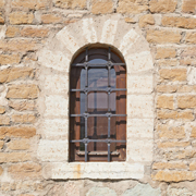 Fortress window with bars in its frame