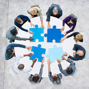 Group of people putting giant jigsaw puzzle pieces together