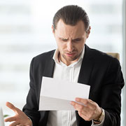 Businessman looking bewildered while looking at a document