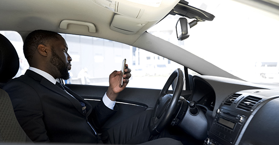 Businessman sitting in a car looking at his phone