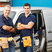 2 construction/maintenance workers standing next to a pickup truck
