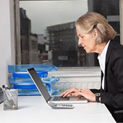 Elderly businesswoman sitting in front of a computer