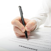 Hand with pen signing an agreement