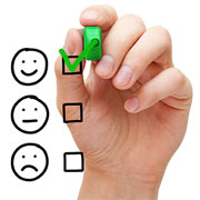 Hand with green marker checking a happy face survey option