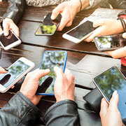 Group of people sitting at a table with their phones out