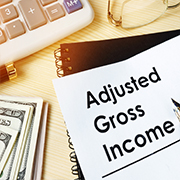 "Calculator, cash, and paper with the text ""Adjusted Gross Income"""