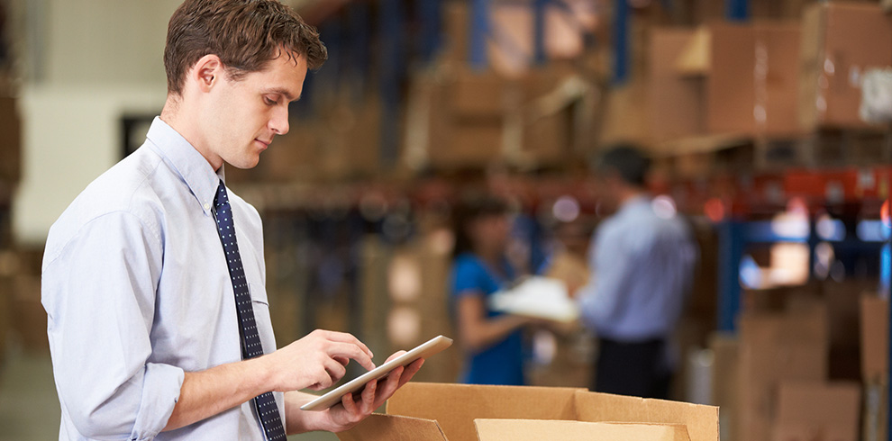 Manager checking inventory with a tablet