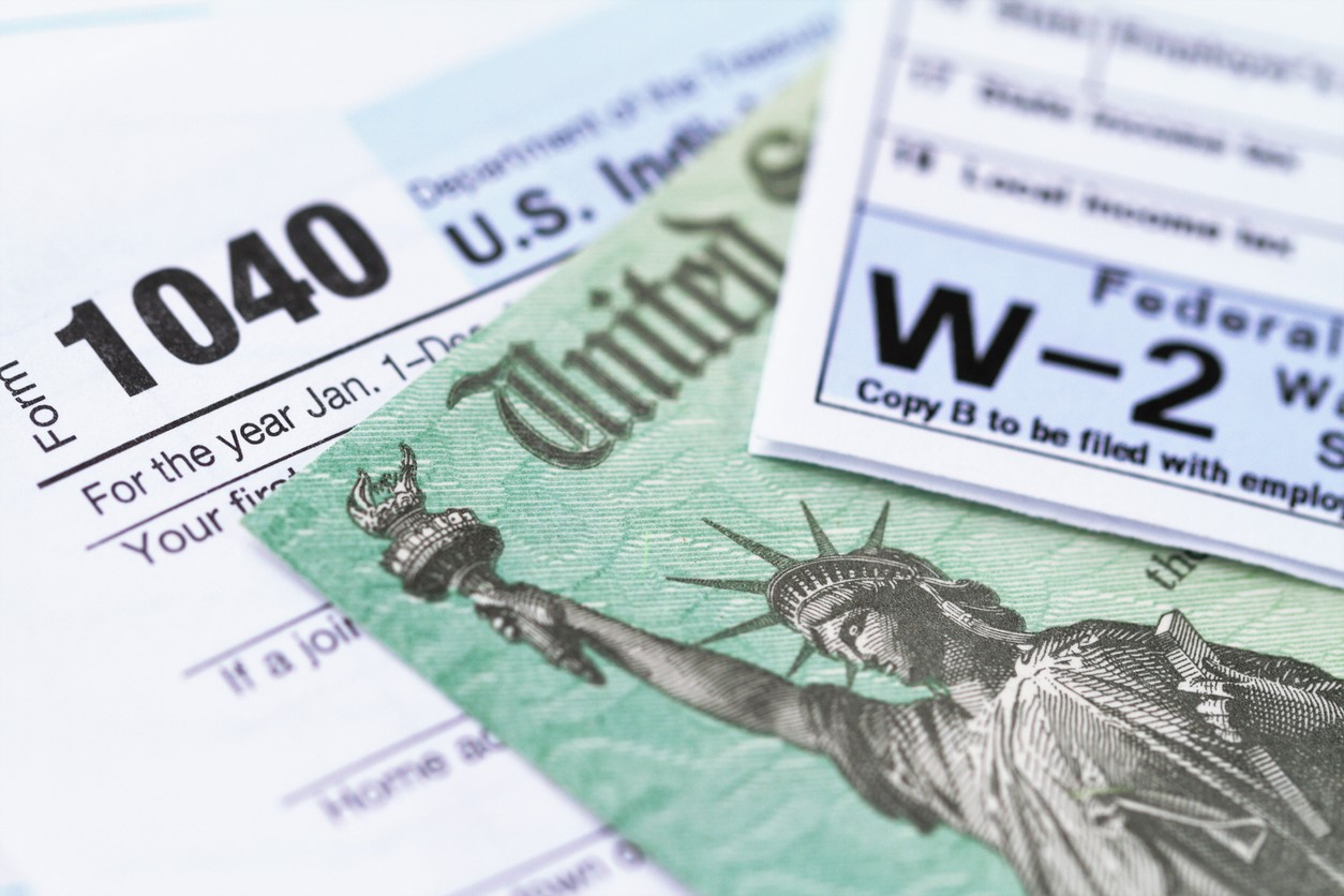 Close-up shot of IRS paperwork like 1040 and W-2 for taxes.