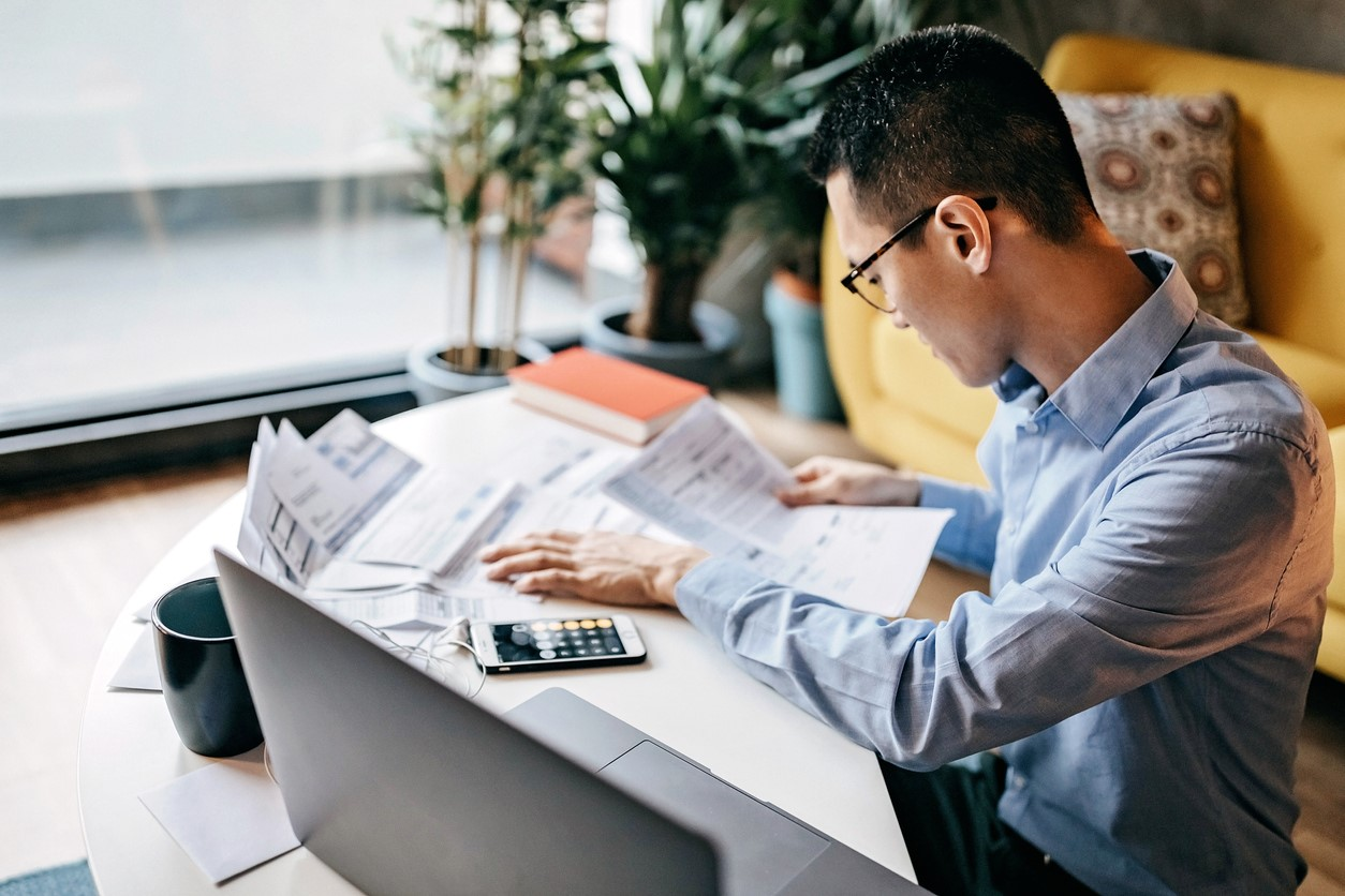 A young professional man sitting at home in front of his computer and doing his taxes.