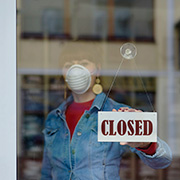 "Woman wearing a mask turning a store ""Closed"" sign"