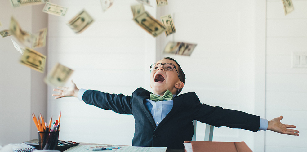 Kid wearing business suite with money floating in the air