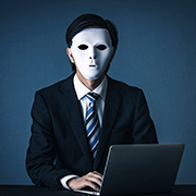 Businessman wearing a white mask sitting in front of a laptop