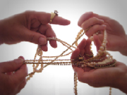 2 pairs of hands grabbing at jewelry and necklaces