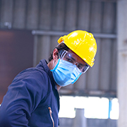 Man wearing a yellow hard hat and a face mask
