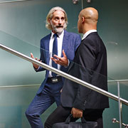 Two businessmen talking while walking up stairs