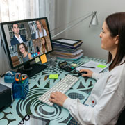 Woman sitting a a desk videoconferencing with 4 other people