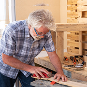 Elderly man sanding a piece of wood