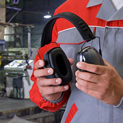 Manufacturing employee holding noise cancelling headphones