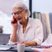 Elderly woman sitting at a desk on a phone call