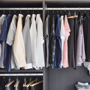 Closet with rows of dress shirts on hangers