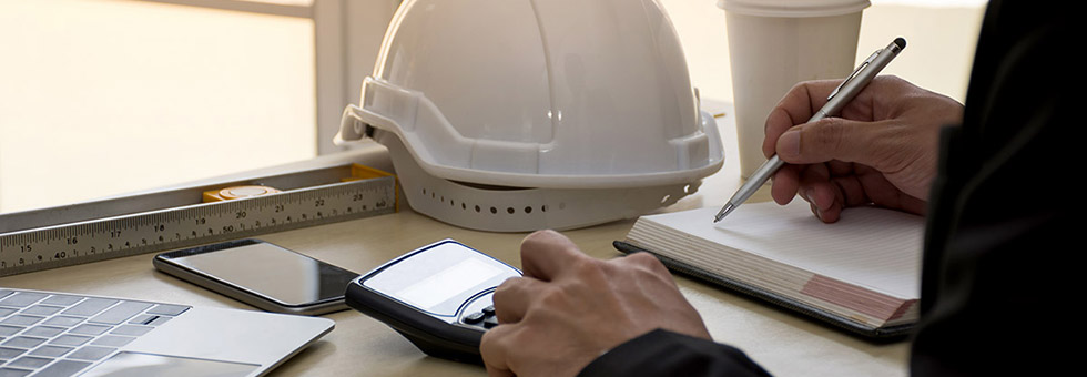 Construction businessman using a calculator and pen and paper